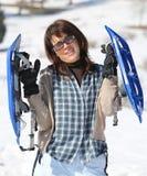 Женщина с snowshoes в горах Стоковые Фото