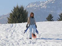 Женщина с snowshoes в зиме Стоковые Фото