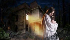 Женщина с spellbook, покинутым домом в ноче Стоковые Фотографии RF