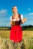 Женщина с tracht, пивом и кренделем в Баварии Стоковые Изображения