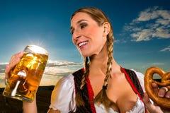 Женщина с tracht, пивом и кренделем в Баварии Стоковые Фото