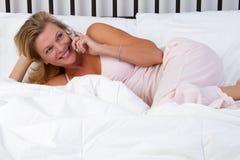 женщина телефона кровати стоковая фотография rf