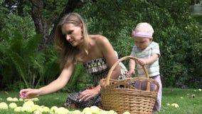 Женщина тратит freetime с дочерью младенца в парке с яблоком 4K сток-видео