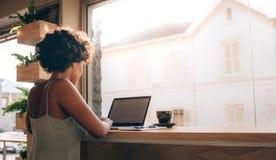 Женщина тратя время на кофейне стоковое фото