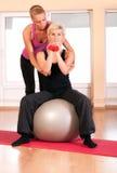Женщина тренера помогая в делать тренировку на шарике Стоковые Изображения RF