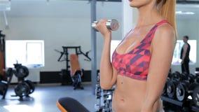 Женщина тренирует ее bicepses на спортзале сток-видео