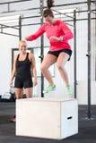 Женщина тренирует скачки коробки с ее командой стоковые фото