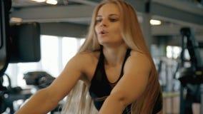 Женщина тренируя ее руки в спортзале используя профессиональное machi разминки акции видеоматериалы