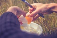 Женщина треская яичко на портативной располагаясь лагерем плите стоковое фото
