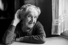 Женщина трудно--слуха пожилая положила ее руку к ее уху стоковая фотография