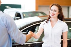 Женщина тряся руки с продавцем автомобилей Стоковые Изображения RF