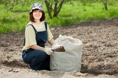 Женщина удабривает почву стоковое изображение