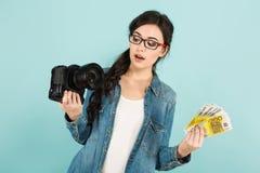 Женщина удивленная детенышами с камерой и наличными деньгами Стоковое Изображение RF