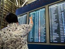 Женщина указывает вверх на табло с план-графиком полетов стоковая фотография