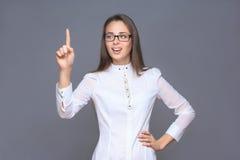 Женщина указывая ее палец на мнимой кнопке Стоковые Фото