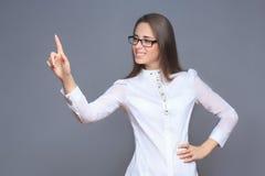 Женщина указывая ее палец на мнимой кнопке Стоковые Изображения RF