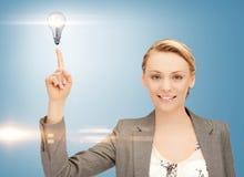 Женщина указывая ее палец на электрическую лампочку стоковое фото