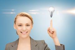 Женщина указывая ее палец на электрическую лампочку стоковые изображения