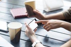 Женщина указывая на белый пустой экран smartphone в кафе Конец-u Стоковая Фотография