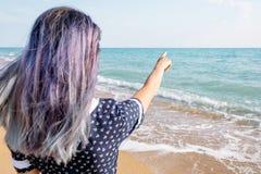 Женщина указывая на море, экземпляр-космос стоковая фотография