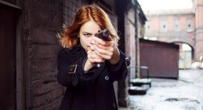 Женщина указывая оружие Стрельба девушки мафии на кто-то на улице Стоковая Фотография