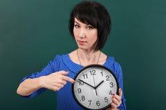 Женщина указывая палец на вахту, представляя доской мела, временем и концепцией образования, зеленой предпосылкой, съемкой студии Стоковое Изображение