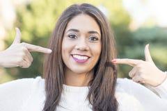 Женщина указывая пальцы на ее улыбка, совершенная белая концепция зубов стоковое изображение rf