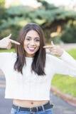Женщина указывая пальцы на ее улыбка, совершенная белая концепция зубов стоковая фотография