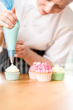 Женщина украшая домодельные пирожные с сливк Стоковые Изображения RF