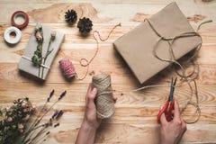 Женщина украшая подарок рождества Стоковые Изображения