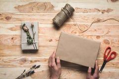 Женщина украшая подарок рождества Стоковое Изображение RF