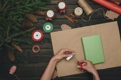 Женщина украшая подарок рождества Стоковые Фотографии RF