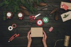 Женщина украшая подарок рождества Стоковые Фото