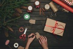 Женщина украшая подарок рождества Стоковая Фотография RF