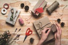 Женщина украшая подарок рождества Стоковые Изображения RF