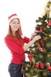 Женщина украшая рождественскую елку над белизной стоковая фотография