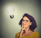 Женщина думает смотреть вверх на яркой электрической лампочке Стоковые Изображения RF