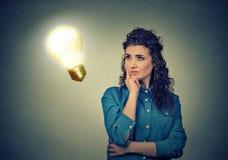 Женщина думая мечтающ смотреть вверх на яркой электрической лампочке Стоковые Изображения