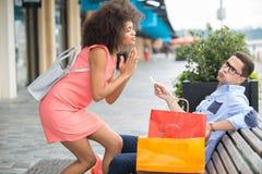 Женщина умоляя партнеру для кредитной карточки пока вне ходящ по магазинам Стоковая Фотография