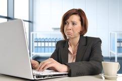 Женщина унылого дела красная с волосами в стрессе на работе с компьютером Стоковые Фотографии RF