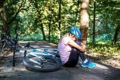 Женщина упала от велосипеда в шлеме травма Концепция o стоковые изображения