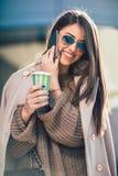Женщина управляет идти на улицу города и говорить на мобильном телефоне держа кофе для того чтобы пойти стоковое фото rf