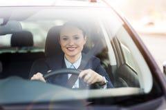 Женщина управляя автомобилем и усмехаться стоковое фото