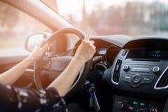 Женщина управляя автомобилем на солнечном дне стоковое изображение