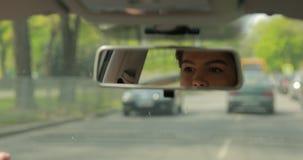 Женщина управляя автомобилем смотря зеркало заднего вида видеоматериал