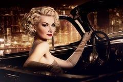 Женщина управляя ретро автомобилем с откидным верхом Стоковые Фото