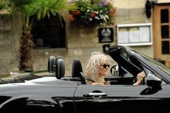Женщина управляя черным автомобилем с откидным верхом стоковые фото