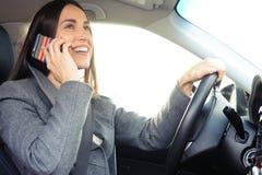 Женщина управляя автомобилем и говоря на smartphone стоковое фото