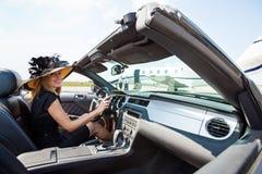 Женщина управляя автомобилем с откидным верхом к частному самолету на Стоковое Фото