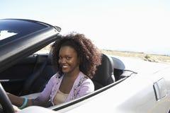 Женщина управляя автомобилем с откидным верхом на дороге пустыни Стоковое Фото